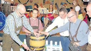 Bürgermeister Michael Franz unterstützt von Tobias Eckert, Christoph Heep und Kai Müller (Musikverein) (v. li.) beim Fassbieranstich.